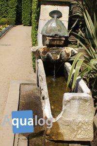 Brunnen in den Römischen Bädern. Das Wasser fließt über eine echte Mördermuschelschale in den Trog.
